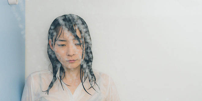 呆然とシャワーを浴びる女性