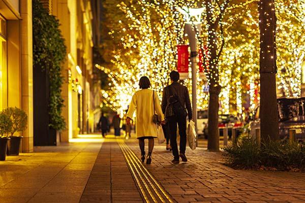 イルミネーションで輝く街で、手をつないで歩く不倫カップル